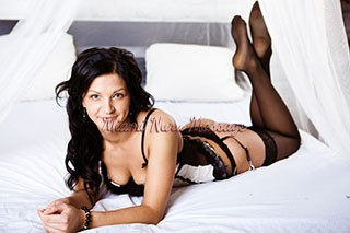 Brunette smiles wearing nothing but panties and a pillow