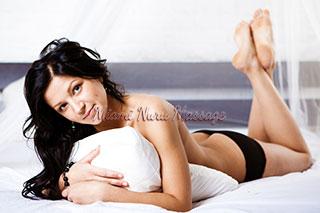 Hot brunette poses in lingerie across the bed